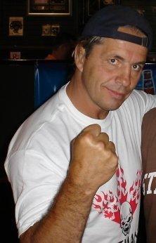 Bret Hart, escondendo o dedo médio para Vince McMahon